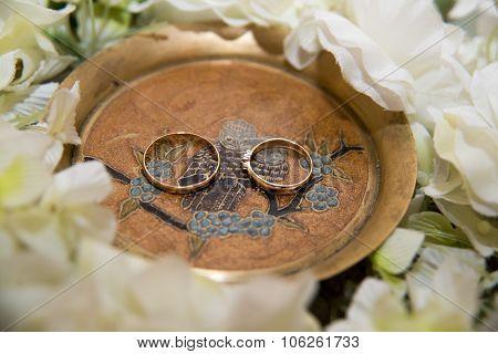 Two  wedding rings lie in treelake near flowers