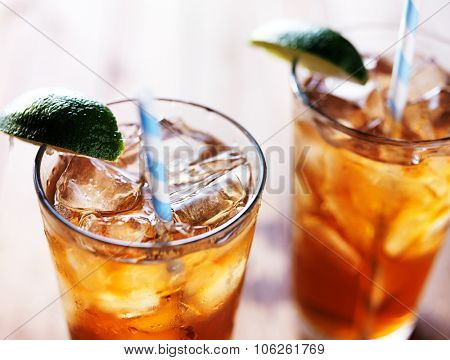 iced tea with lime wedge and retro paper straws close up