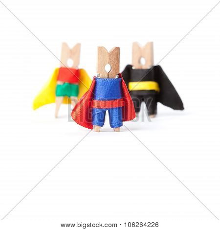 Success leadership conceptual image. Superheroes clothespins. White background