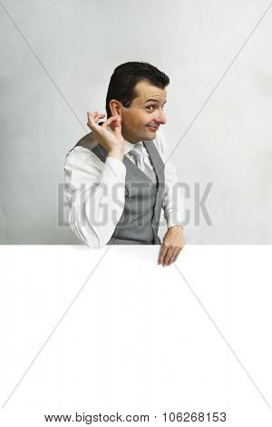 Brazilian man holding earlobe behing a advertising with a copyspace.