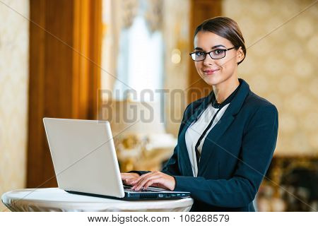 Photo of business woman in expensive hotel. Young business woman wearing suit and glasses, standing in nice hotel room, using laptop and looking at camera poster