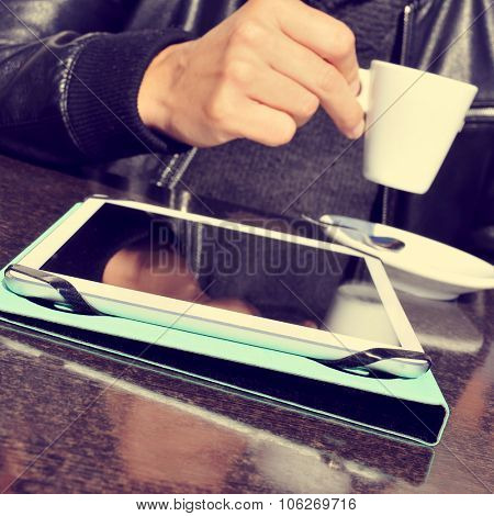 closeup of a young man taking a cup of coffee with a tablet computer on the table, in the terrace of a cafe