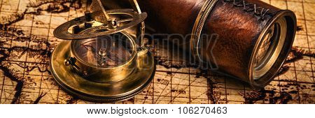 Travel geography navigation concept background - letterbox panorama of old vintage retro compass with sundial and spyglass on ancient world map