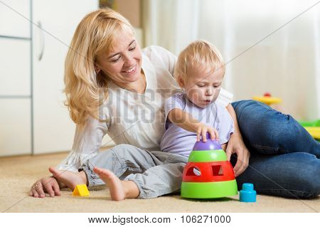 mother and her child playing with colorful logical toy