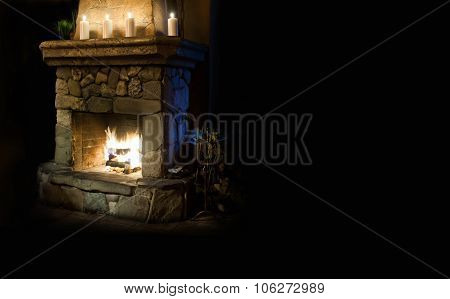 Chimney place with candles  and flame. Copy space, black background
