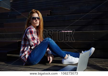 Female student preparing for lectures while using her net-book on campus