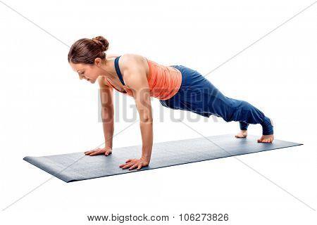 Young fit sporty woman doing Hatha yoga asana Utthita chaturanga dandasana - extended four-limbed staff (plank) pose isolated