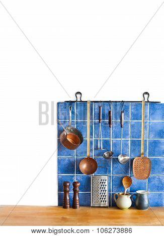 Kitchen interior, accessories. Hanging copper kitchenware set. Spoon, skimmer, colander.