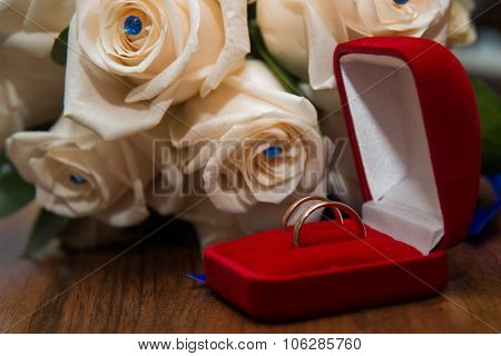 Two wedding rings in red box lying on the bouquet of white roses