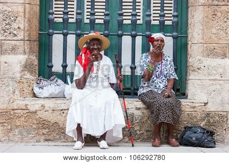HAVANA, CUBA - JULY 17, 2013: Cuban ladies dressed in typical clothes posing for photos while smoking a huge cuban cigars in Havana, Cuba.