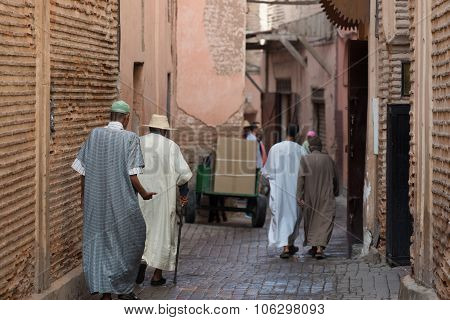 traditionally clothed moroccans walking in the medina poster