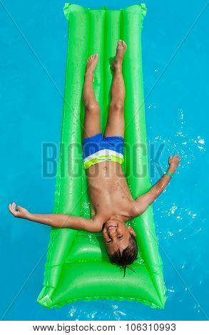 Happy boy relaxing on green inflatable mattress