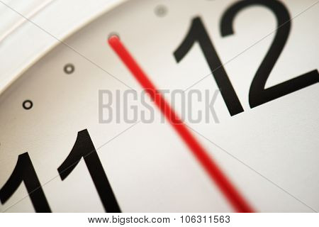 Timing or moment. Waiting for the right timing. Few minutes or seconds to the hour. Focus on clock face letter (needle has blur/ movement).  Extremely shallow depth of focus. Impression shot.   poster