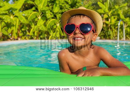 Boy in heart-shaped sunglasses on green airbed