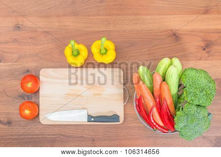 Resh Vegetables And Knife On Cutting Board On Wood Table