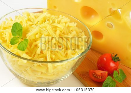 close up of grated cheese in glass bowl and wedge of cheese on wooden cutting board