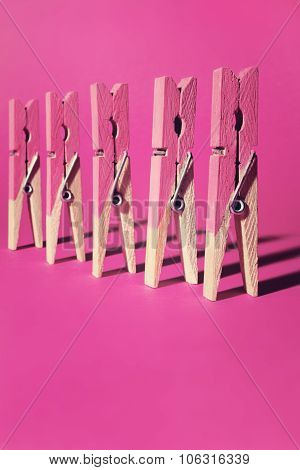Row Of Pink Painted Clothes Pegs On Pink Background