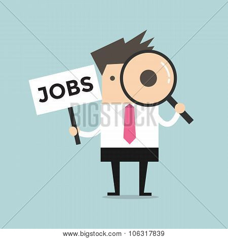Businessman looking through a magnifying glass with Jobs Sign