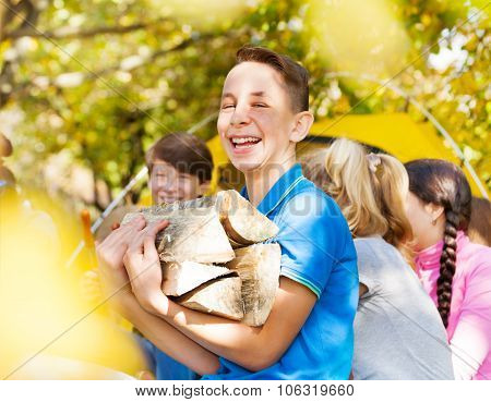 Laughing boy holding kindling wood on campsite