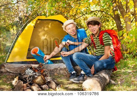 Teen boys sit on campsite with sausages sticks