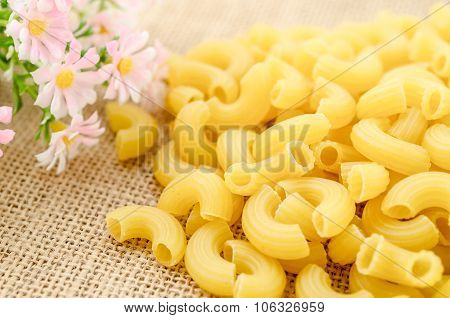 Elbow macaroni noodles with flower on sack background. poster