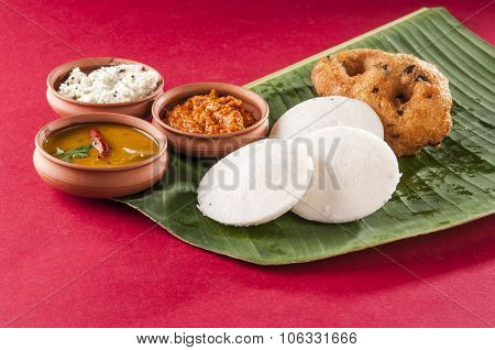 South Indian food idli vada with sambar and chutney on a banana leaf, on red background