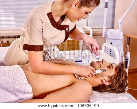Man receiving electric facial peeling hydradermie at beauty salon.  poster