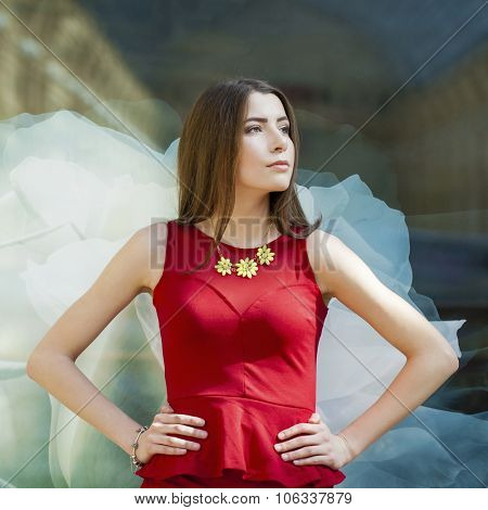 Sultry portrait of sexy brunette in a red dress on a background of a wall
