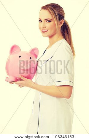 Young beautiful female doctor holding a piggybank.