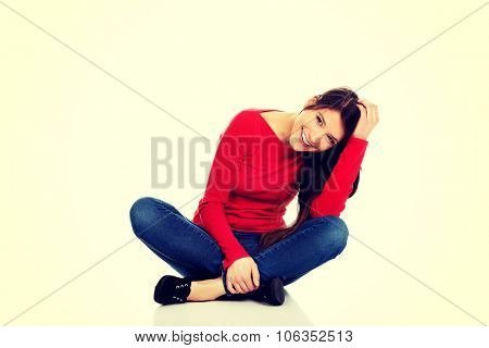Student woman sitting cross legged on the floor.