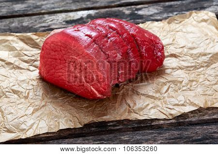 A Pieces Of Fresh Meat, Beef Slab On Crumpled Paper On Old Wooden Table. Ready To Cook.