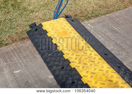 The Electric Cable Are Protectd By Grunged Plastic Speed Bump In A Roadwork.