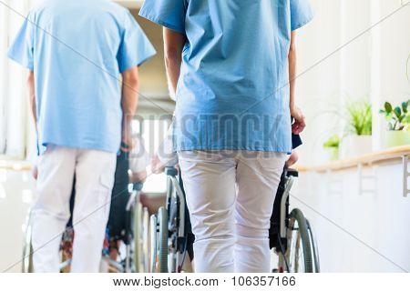 Nurses pushing seniors in wheelchair thru nursing home