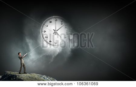 Young businessman trying to turn back time by pulling clock with rope
