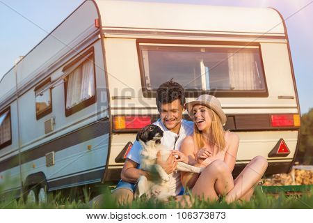 Beautiful young couple in front of a camper van on a summer day poster