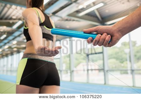 Man passing the baton to partner on track at the gym