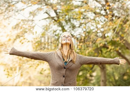Smiling pretty woman with arns outstretched on an autumns day