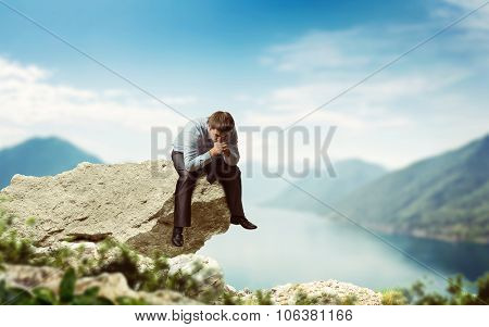 Frustrated businessman sits on edge of the cliff poster