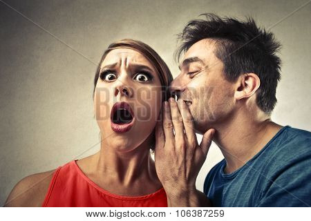 Man whispering into a woman's ear