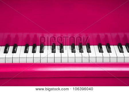 Piano keys of pink piano close up