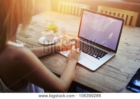 Blonde female student working on net-book after her lectures in Universityflare sun