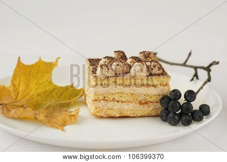 white cake with cocoa and chokeberry maple leaf