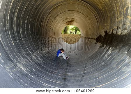 Child Sitting In The Tunnel And Rear Benches Under Trees