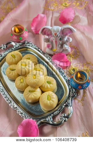 Indian sweets and a small statue of Ganesha. poster