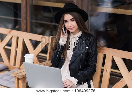 Hipster girl dressed in classy clothes calling with cell telephone during work her on net-book