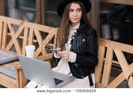 Stylish woman using cell telephone while resting after work on net-book