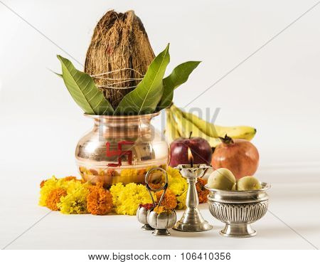 copper kalash with coconut and mango leaf with floral decoration, fruits, diya, sweet pedha,essentia