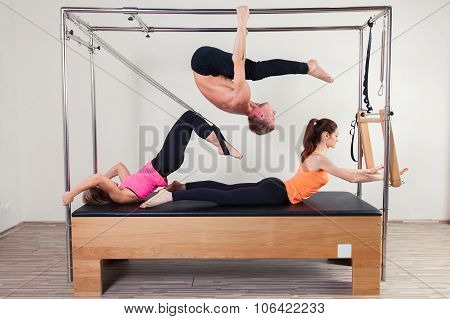 Pilates aerobic instructor a group of three people in cadillac fitness exercise. poster