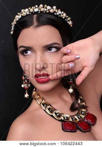 fashion studio portrait of gorgeous woman with dark hair and bright makeup with luxurious bijou massive necklace and headband poster