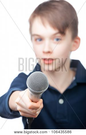 Boy holding a microphone conducting an interview, focus on microphone face is blurred